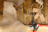 Working place of florist.Composition with sackcloth, pruner, twine and tags. Conceptual photo — Stock Photo