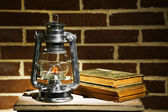 Burning kerosene lamp and books on brick wall background — Stock Photo