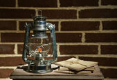 Burning kerosene lamp and letters on brick wall background — Stock Photo