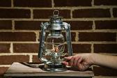 手はレンガ壁の背景の灯油ランプを点灯します。 — ストック写真