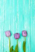 Hermosos tulipanes sobre fondo de madera color — Foto de Stock