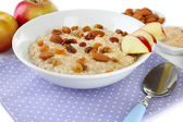 Tasty oatmeal with raisins and apples close up — Stock Photo