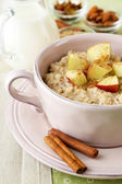 Tasty oatmeal with apples and cinnamon on table close up — Stock Photo
