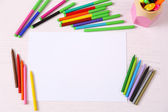 Colored pencils and blank paper sheet on wooden table — Stock Photo
