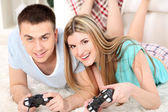 Couple playing video games on home interior background — Zdjęcie stockowe