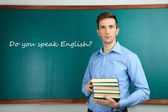 Young teacher with books near chalkboard in school classroom — Stock Photo