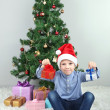 Little boy with gifts near Christmas tree in room — Stock Photo