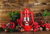 Red kerosene lamp on wooden table on wooden background — Stock Photo