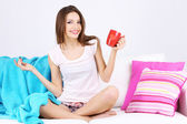 Beautiful young woman sitting on sofa with red cup on gray background — Stock Photo