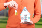 Little paper house in hand close-up, on bright background — Stock Photo