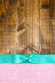 Colorful fabric with color ribbon and bow on wooden background — ストック写真