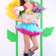 Beautiful young woman in petty skirt holding basket of flowers on decorative background — Stock Photo #43900207