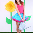 Beautiful young woman in petty skirt holding watering can on decorative background — Stock Photo #43900317