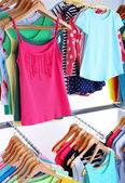 Different clothes on hangers on light background — Stock Photo