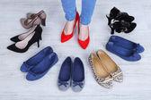 Meisje kiest schoenen in de kamer op grijze achtergrond — Stockfoto
