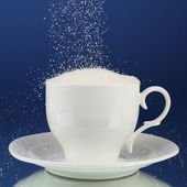Sugar in cup on blue background — Stockfoto