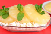 Bowl of tasty cottage cheese with pineapple, on red background — Stock Photo