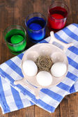 Eggs with liquid colour in glass on table close up — Stockfoto