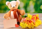 Urso de brinquedo na mesa no fundo brilhante — Fotografia Stock