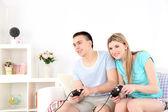 Par som spelar tv-spel på hem inredning bakgrund — Stockfoto