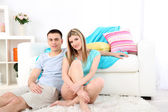 Loving couple sitting on carpet near sofa, on home interior background — Stock Photo