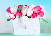 Beautiful tulips  in wooden box, on light background — Stock Photo