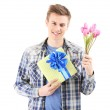 Portrait of handsome young man with flowers and gift, isolated on white — Stock Photo #43960877
