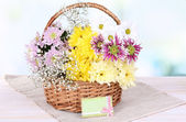 Beautiful chrysanthemum flowers in wicker basket on table on light background — Stock Photo