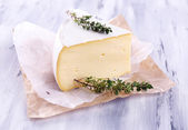 Tasty Camembert cheese with thyme, on wooden table — Stock Photo