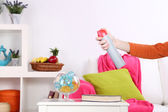 Sprayed air freshener in hand on home interior background — Zdjęcie stockowe