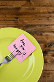 Note paper with message  attached to fork, on plate, on wooden background — Stock Photo