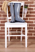 Pair of colorful gumboots on chair on color wall background — Stockfoto