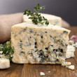 Tasty blue cheese with thyme, on wooden table, on grey background — Stock Photo #43993155