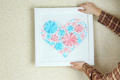 Woman hanging up picture with heart from paper flowers  — Stockfoto