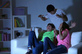 Young friends watching horror movie at home of blacking-out — Foto de Stock