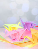 Origami cranes on wooden table, on light background — Stockfoto