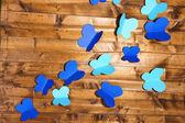 Carta tagliata fuori farfalle, su fondo in legno — Foto Stock