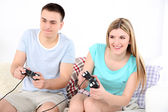 Couple playing video games on home interior background — Stok fotoğraf