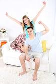 Loving couple sitting on sofa, on home interior background — Stock Photo