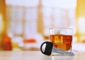 Composition with car key and glass of whiskey, on wooden table, on bright background — Foto de Stock