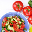 Fresh salad with tomatoes and cucumbers on white wooden background — Stock Photo #44088869