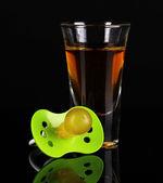 Baby dummy with alcoholic beverage isolated on black — Stock Photo
