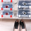 Shoes in plastic boxes and female shoes on floor in room — Stock Photo #44090603
