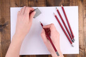Hands holding pencil and erase with paper on wooden background — Stock Photo