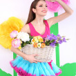 Beautiful young woman in petty skirt holding basket of flowers on decorative background — Stock Photo #44187845