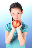 Portrait of beautiful little girl with apple on blue background — Stock Photo