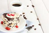 Söt kaka med choklad på plattan och kopp kaffe på träbord — Stockfoto
