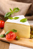 Tasty Camembert cheese with tomatoes, olives and basil, on wooden table — Stock Photo