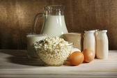 Tasty dairy products on wooden table, on sacking background — Stock Photo