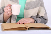 Woman reading book and  drink coffee or tea, close-up — Stock Photo